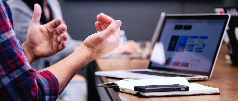 hands in front of a laptop in an asking a question gesture