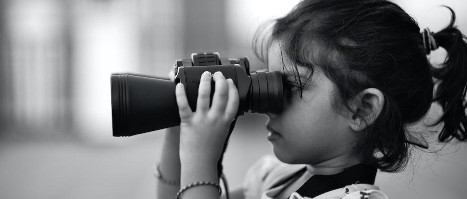 Little girl looking through binoculars.